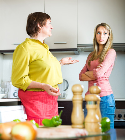 squabble: Mature mother arguing in the kitchen with her ​​adult daughter