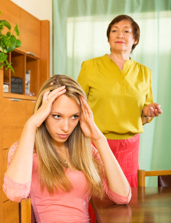 fracas: Elderly  mother and  adult daughter  after quarrel in home  interior Stock Photo