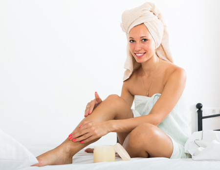 foot cream: Blonde girl applying  foot cream on legs in bed at home Stock Photo
