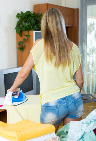 ironing board: Blonde long-haired woman ironing at ironing board in home