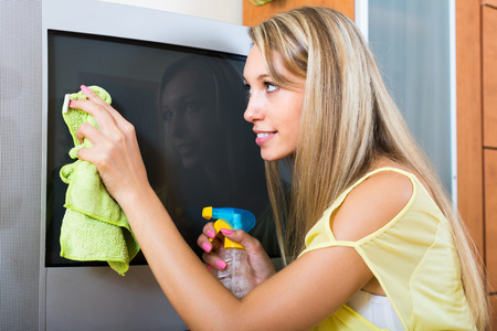 domestic task: Blonde young girl cleaning TV with cleanser at home