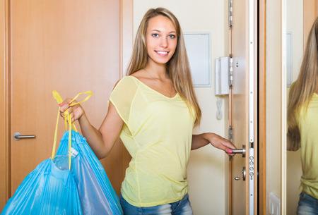 Glückliche gewöhnliche Frau zu bleiben an der Tür mit Müllbeutel Standard-Bild - 37579328