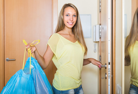 cleaning service: Happy ordinary woman staying at the door with trash bags