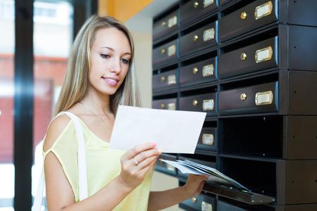 buzon: Muchacha rubia sonriente tomando correo basura la caja de publicación