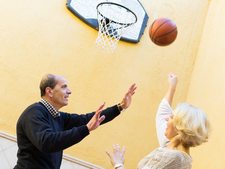 Positive mature spouses throwing the ball into basket photo