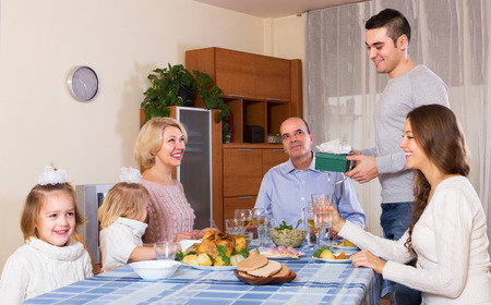 relatives: Smiling young family member receiving present from relatives at table