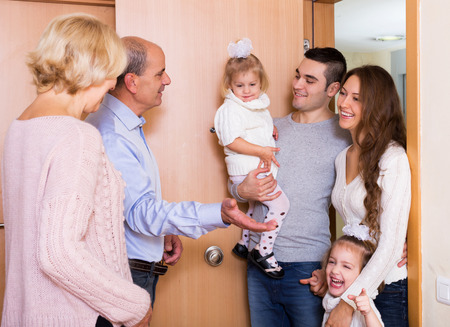grand parents: Positive young family with two daughters visiting grand parents