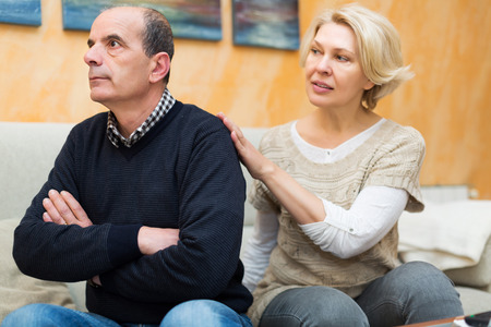 husband: Guilty senior wife asking husband for forgiveness at home Stock Photo