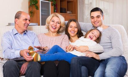 familias unidas: Sonreír grandes miembros de la familia unidos juntos en la sala de estar