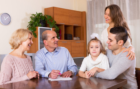 happy home: Happy family members ready to sign banking documents at home or office