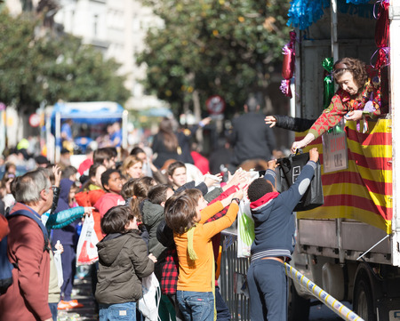BARCELONA, SPAIN - MARCH 3, 2015: Children collecting caramels from car.  Sant Medir - event, during which participants were given tons of caramels Editorial