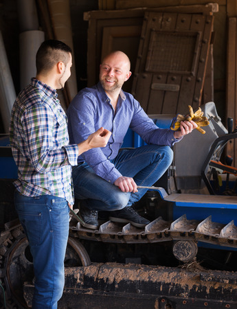 Two adult smiling male drivers working with tractor and chatting