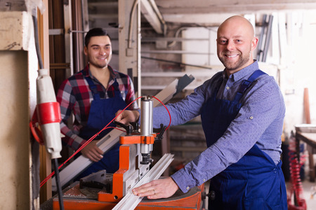 enginery: Two smiling workers in uniform working on machine in PVC shop
