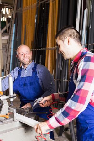 toolroom: Two positive workmen in uniform working on machine in PVC shop indoor