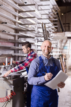 glasswear: Two workers in coverall working with glass in store