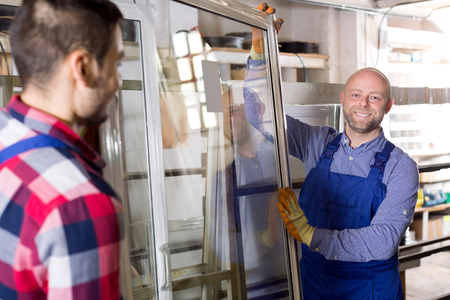 window: Two workmen in blue overalls with windows production at modern factory
