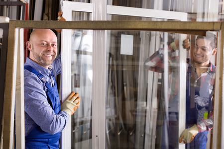 glasswear: Couple of workmen inspecting windows at workshop Stock Photo