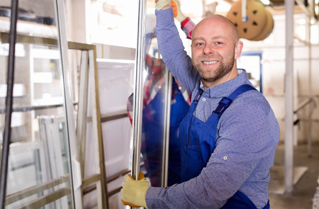 toolroom: Two happy workers inspecting windows at workshop Stock Photo
