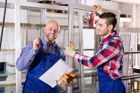 toolroom: Smiling couple of workmen inspecting windows at workshop