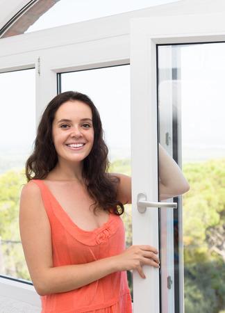 opening window: Mujer joven ventana de apertura y sonriente Foto de archivo