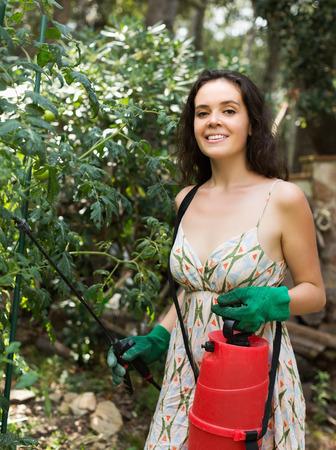 knapsack: Girl working in garden with knapsack garden spray