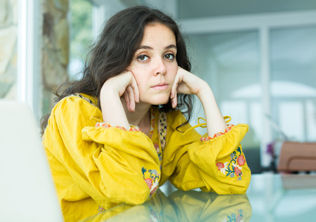 ennui: Young long-haired woman in bright blouse sitting sad at home