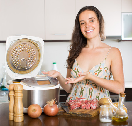 Young woman cooking meat with new electric multicooker at home photo