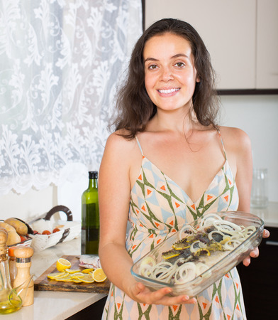 fryingpan: Smiling young housewife putting pieces of lemon in fish at home kitchen Stock Photo