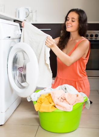 Thuis was. Lachende jonge huisvrouw met wasmachine thuis Stockfoto