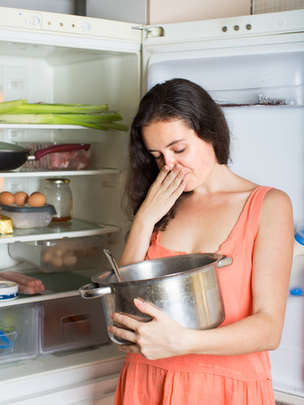 frowy: Brunette  female  holding her nose because of bad smell near fridge at home