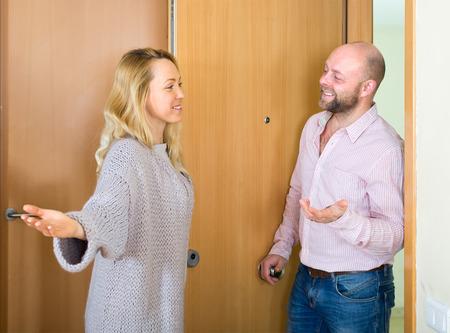 Giovane e bella donna invita ospite maschile a venire nel suo appartamento