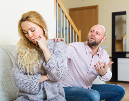 appease: Man consoling the depressed woman on sofa at home Focus on girl