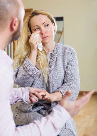 solace: Man tries reconcile with depressed woman after quarrel. Focus on girl