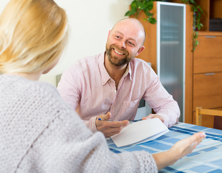Positive smiling couple discussing details of marriage settlement indoors photo