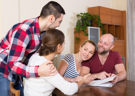 spouses: Young spouses sitting with documents and asking friends for advice Stock Photo