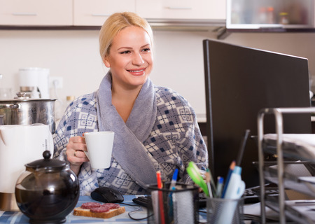 adult sandwich: adult female freelancer with PC, tea and sandwich at kitchen table