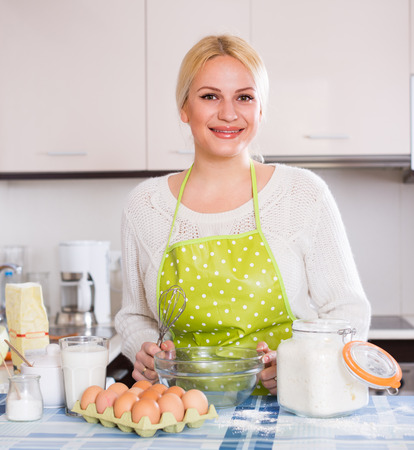 fryingpan: Woman making dough with whisk in home kitchen Stock Photo