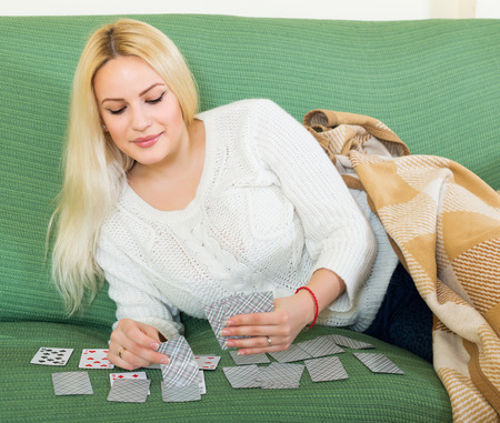 predictor: Relaxed housewife on couch telling fortunes by cards indoors