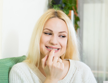 conceive: Portrait of positive young russian woman with finger over lips Stock Photo