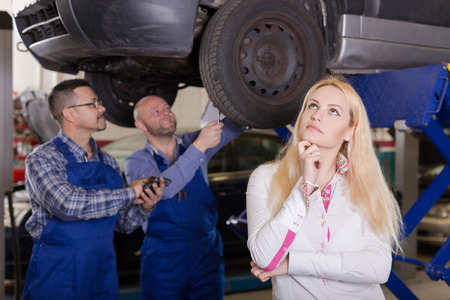 trickery: Two mechanics trying to cheat sad american female client at workshop