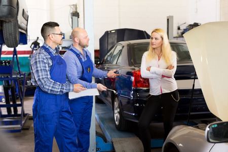 specialists: Sad young girl talking with specialists at auto repair shop. Focus on the men Stock Photo