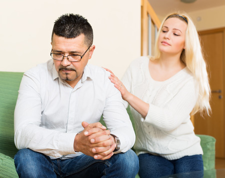 appease: Man has problem, young woman comforting him in the living room at home