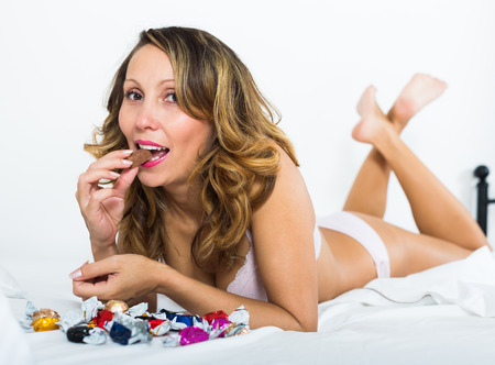 furtively: Smiling long-haired adult woman eating candy in bed at home