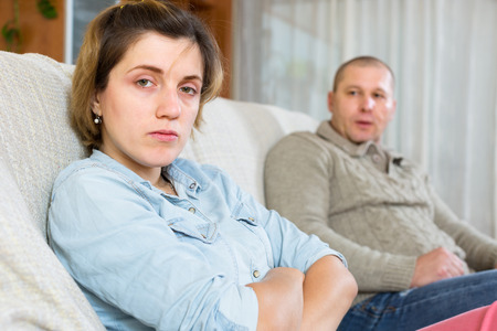 grievance: Family quarrel. Sadness man against unhappy young woman Stock Photo