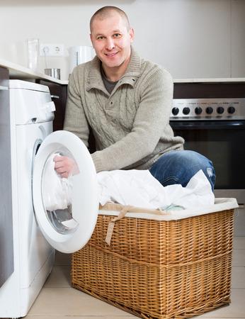 limpieza  del hogar: Inicio de lavandería. Hombre sonriente feliz usando lavadora en la cocina en casa