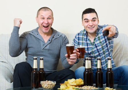 fandom: Adult friends sitting at table with beer and commenting sport tv channel Stock Photo