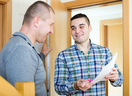lodger: Smiling lodger talking neighbor with papers at doorway. Focus on the right man