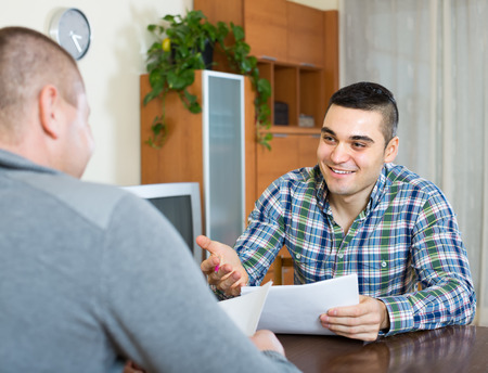 home  life: Young smiling male agent explaining to client terms of life insurance at the table at home Stock Photo
