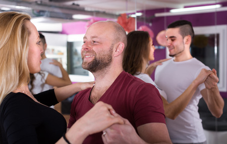 Happy smiling people having dancing class indoors
