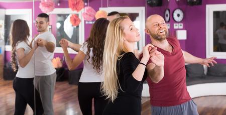 bailarines de salsa: Grupo sonriente de los adultos j�venes bailando salsa en la clase de baile. Centrarse en la ni�a